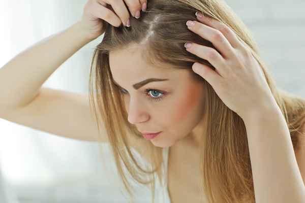 Łojotokowe zapalenie skóry - młoda kobieta przyglądająca się swojej skórze głowy